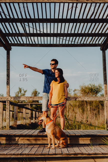 Content casual young man and woman keeping on leash playful brown dog while standing at wooden terrace in rural countryside at sunset