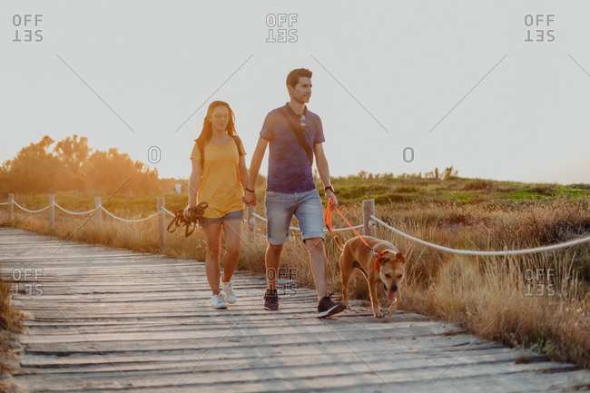 Casual adult couple walking with dog along rural pathway