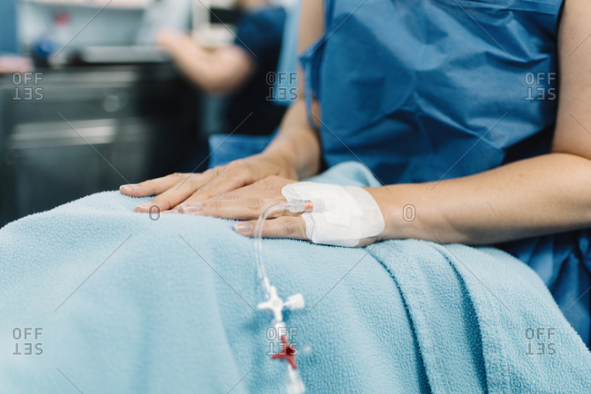 Crop female patient sitting with covered legs and intravenous fluid needle in hand before surgery in operating room