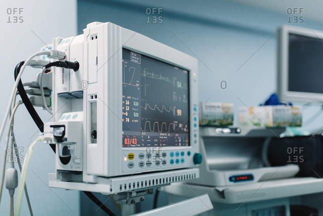 Medical equipment with screens showing vital signs of patient in hospital and boxes with gloves
