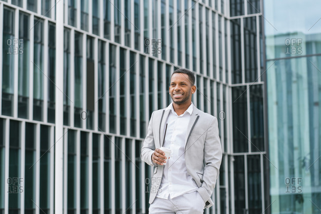 Elegant African American businessman holding coffee and looking along at business center in downtown