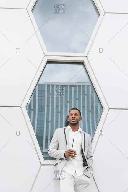 Black man with coffee standing in downtown