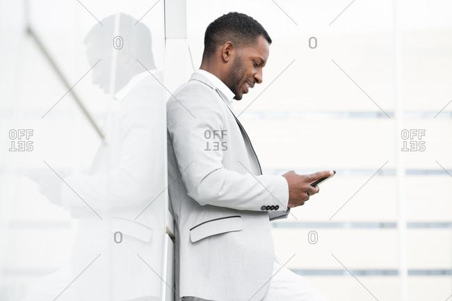 Elegant black man browsing smartphone leaning on geometrical wall
