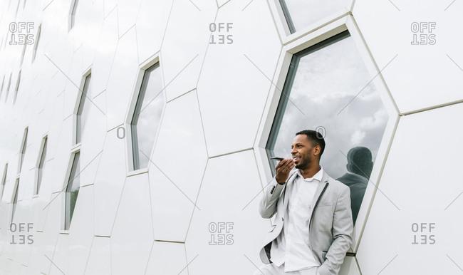 Elegant black man talking smartphone leaning on geometrical wall