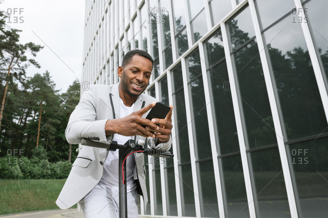 Smiling black man riding scooter and speaking on smartphone