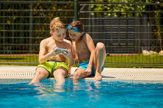Boys on poolside taking selfie