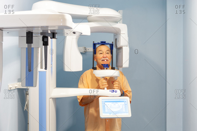 Old man in special protective clothes taking x-ray in dental cabinet