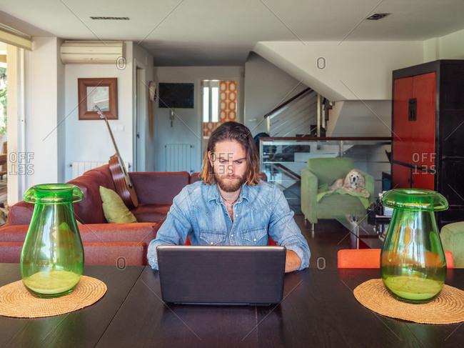 Focused man using computer in apartment