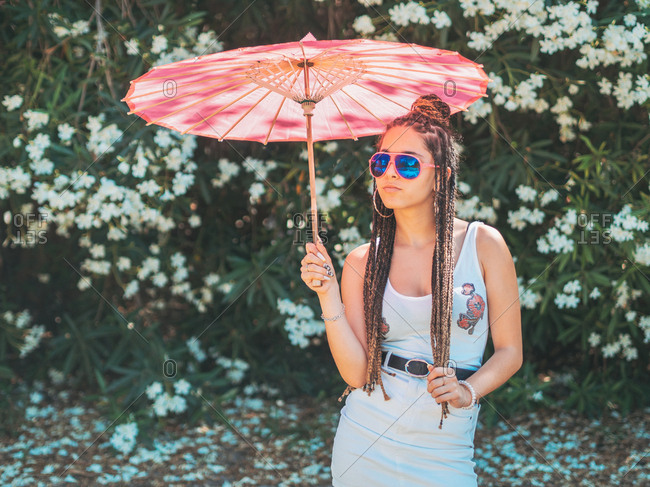 Beautiful slim young woman in summer outfit sunglasses and with umbrella standing legs crossed near blooming trees