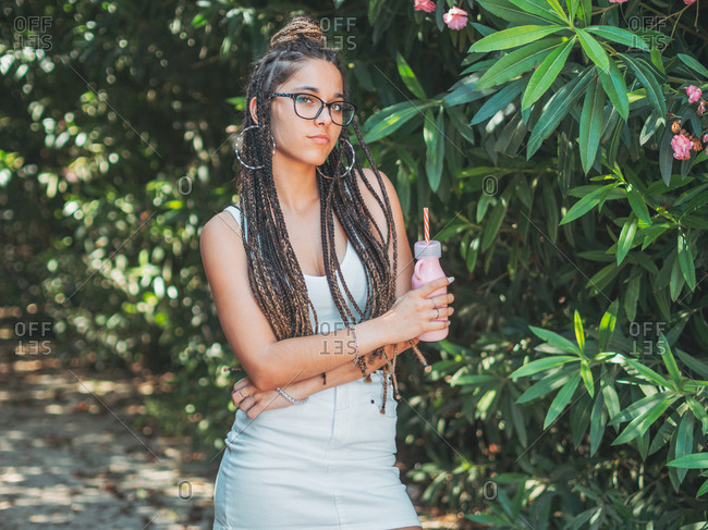 Trendy young female in sunglasses with dreadlocks drinking cocktail and looking at camera
