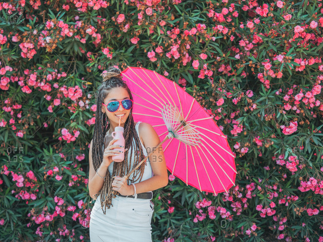Beautiful slim young woman in summer outfit sunglasses and with umbrella drinking beverage near blooming trees