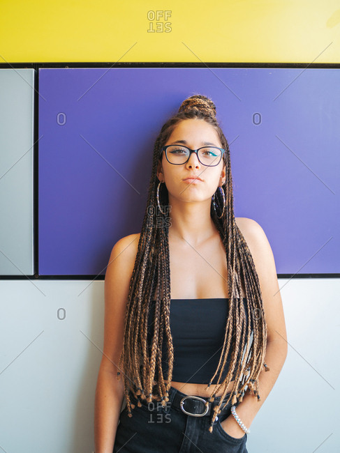 Pretty stylish teenage girl with hands in pocket and unique braids looking at camera on colorful background