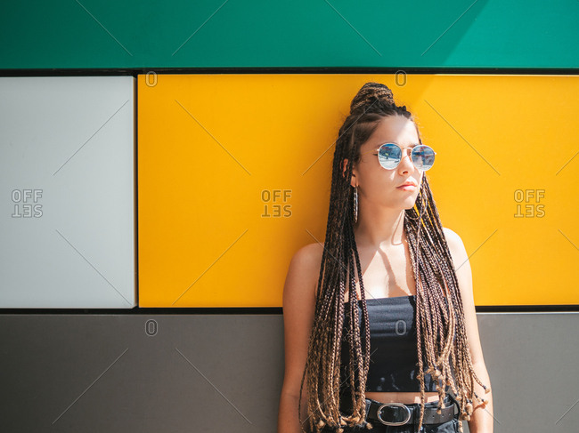 Pretty stylish teenage girl with hands in pocket and unique dreadlocks looking away on colorful background