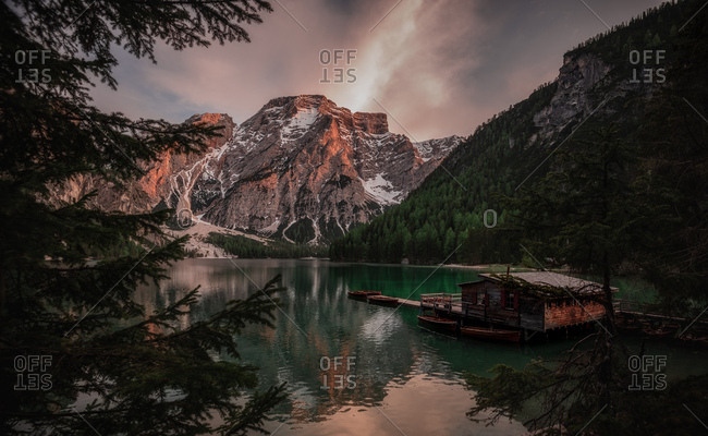 Houseboat surrounded with mountains on serene lake