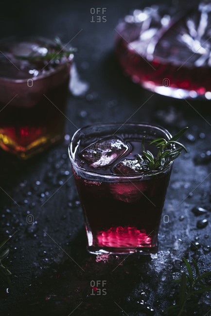 Carafe and crystal glasses with ice filled with red wine on black table