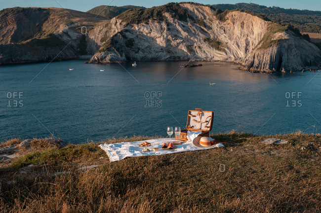 Picnic mat with romantically set with glass of drink and food on dry shore with serene water and hills