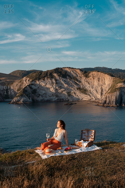 Side view of woman in hat with glass of drink sitting on mat for picnic on dry shore and romantically with eyes closed near serene water and hills