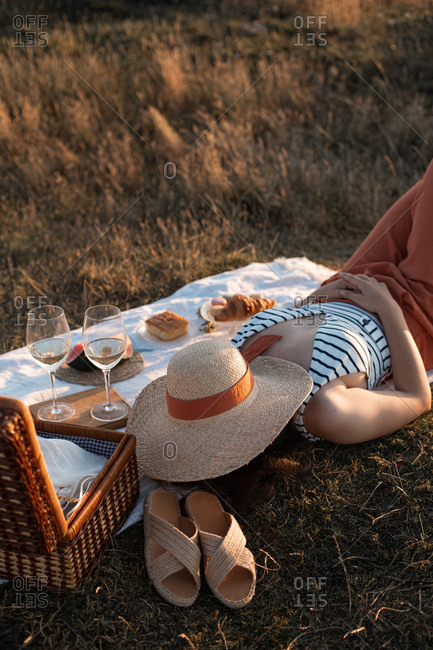From above woman enjoying lying on white picnic mat with hat on face nearby basket on lawn