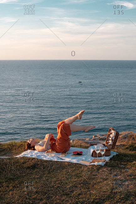 From above woman enjoying lying on white picnic mat holding hat nearby basket on lawn with closed eyes
