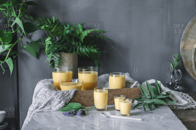 Tasty aromatic mango mousse in glass mugs and spoon on table decorated with green plants