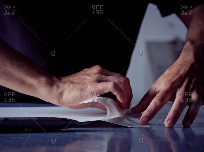 Crop skillful agile craftsman neatly gluing pages together on working table