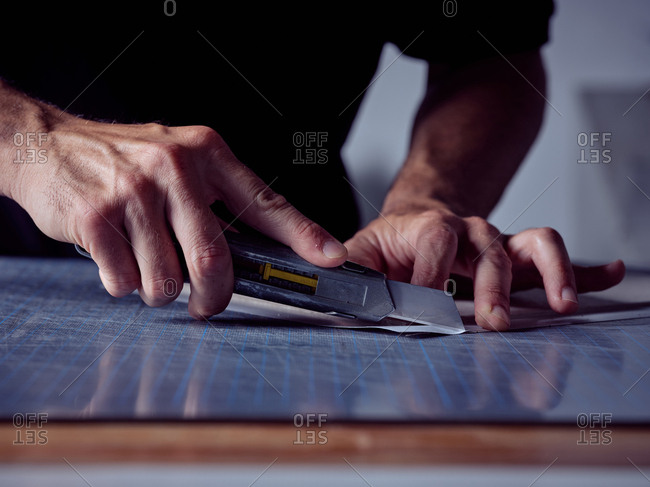 Crop professional man cutting paper sheets with special sharp knife on working table