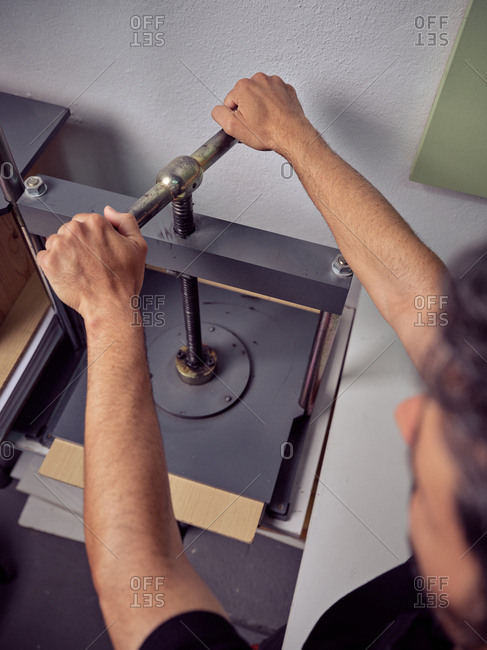 Unrecognizable worker using pressing machine in printing house