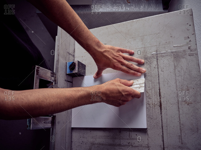 Faceless employee working with paper in printing house