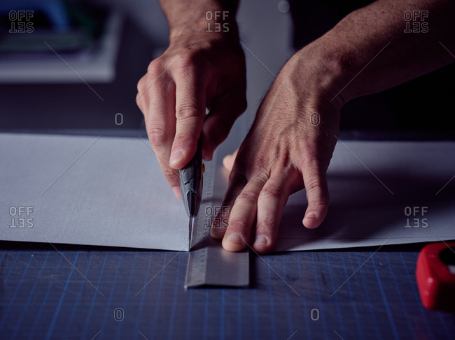 Worker cutting sheet with stationery knife on surface