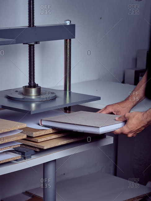 Faceless employee using pressing machine in printing office