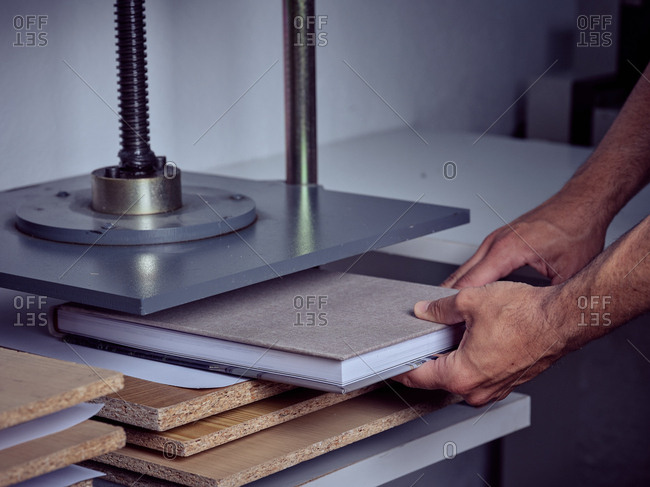 Crop anonymous employee putting book in pressing machine with screw in printing office