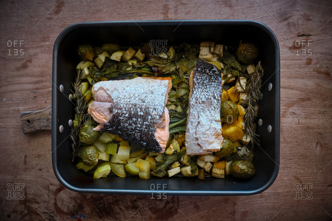 From above roasting pan with large pieces of salmon with skin on garnish of assorted baked vegetables and greens