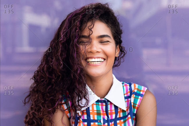 Portrait of charming young ethnic young woman with curly hair with closed eyes near colorful glass wall