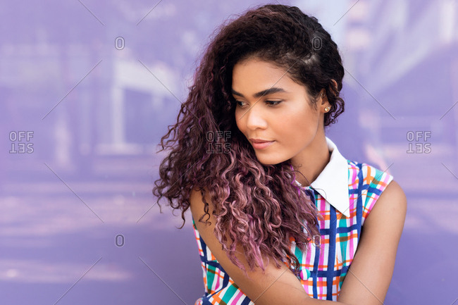 Portrait of charming young ethnic young woman with curly hair tilting head and looking away against colorful glass wall