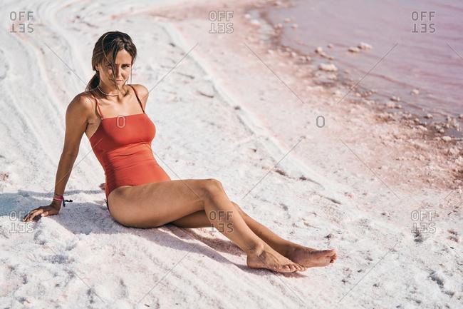 Tanned female in swimwear relaxing on salty lake shore