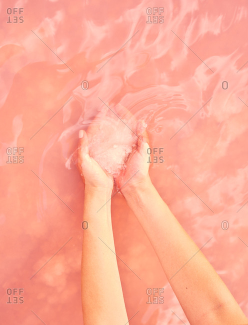 Female holding healing salt pile in pink water