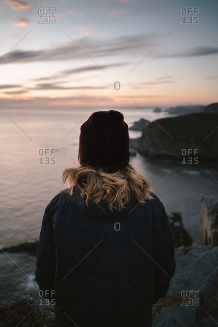 Blonde girl wearing a beanie and a down jacket watching the sunrise by the ocean