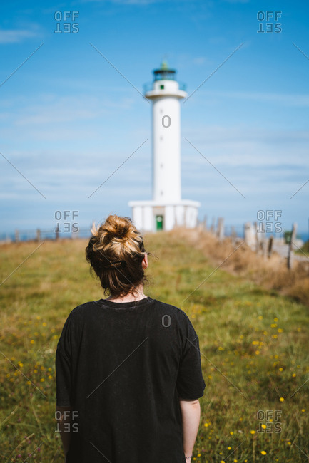 Young girl in black shirt in front of a white lighthouse