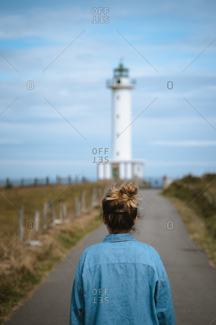 Girl in a blue shirt walking on a road towards a lighthouse