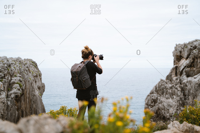 Young traveler girl with a backpack taking a photograph of the coast in Asturias