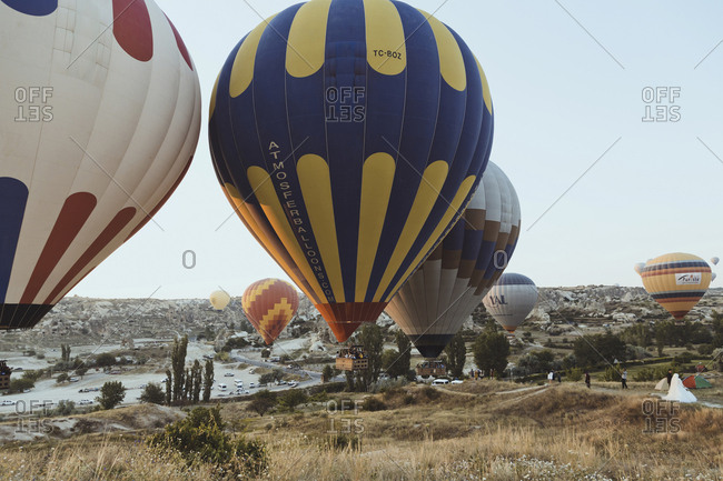 August 22, 2019: Cappadocia, Turkey - Jul 31, 2019: People watching hot air balloons at Cappadocia