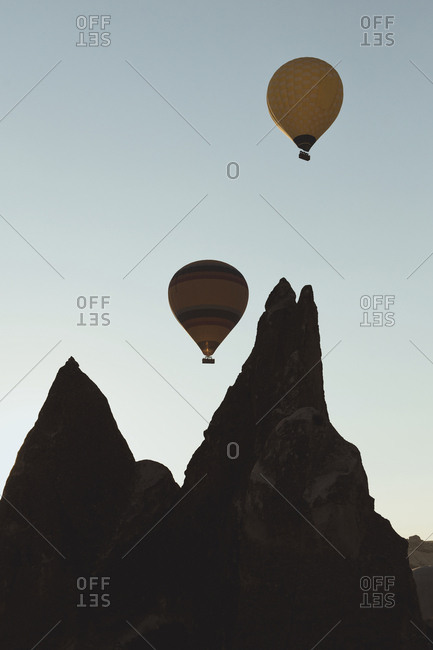View of silhouette of rock shapes with hot air balloon in the distance., Turkey, Cappadocia, Goreme,