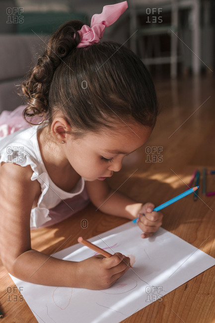 Little girl with tutu lying on the floor paints a sheet with colored pencils