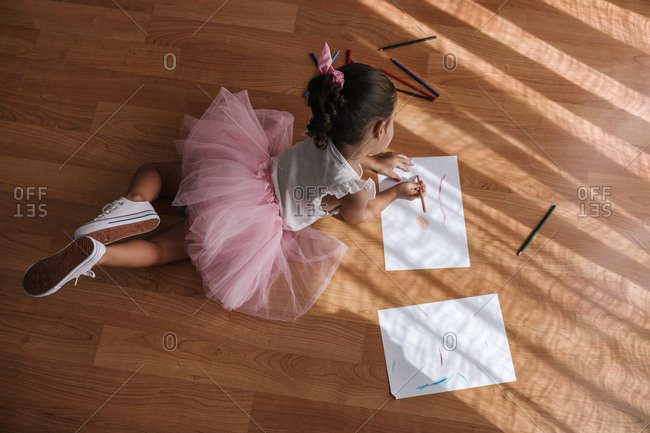 Bird's eye view of girl with tutu drawing on a paper with colored pencils