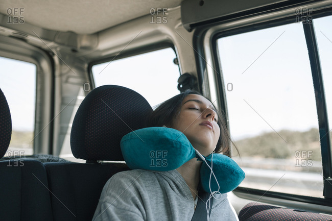 Teen girl sleeping in the car with a pillow on her neck