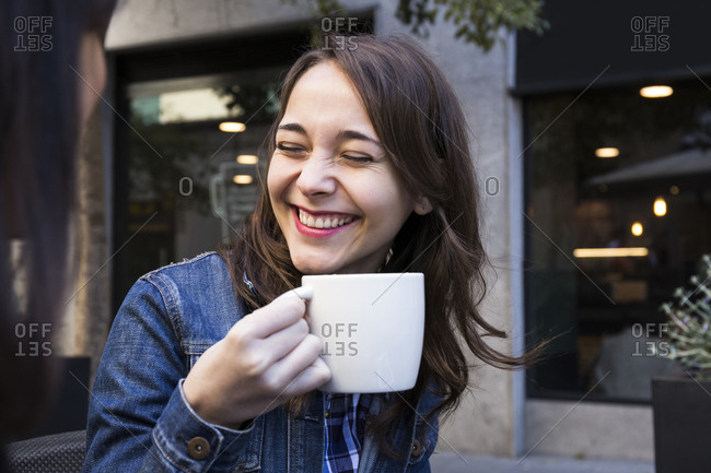 Happy young woman laughing with eyes closed and holding coffee cup in outside cafe in Madrid- Spain