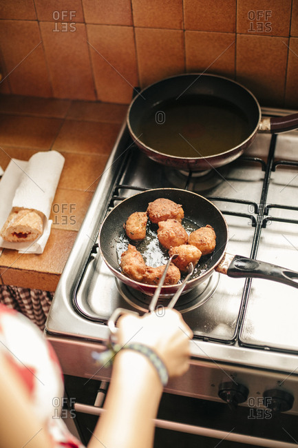 Close-up of a woman cooking croquettes in a pan