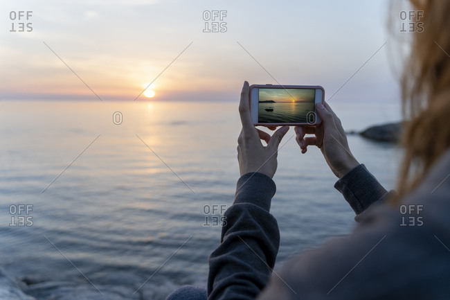 Spain- Costa Brava- Close-up of woman photographing sea at sunrise with smartphone