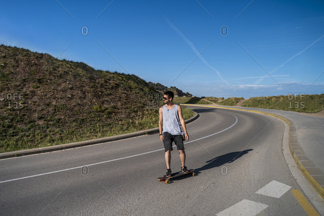 Young man long boarding on empty country road