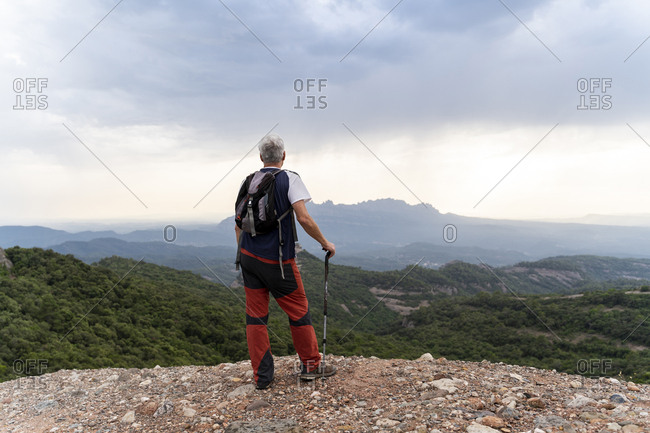 Senior hiker with hiking pole standing on viewpoint
